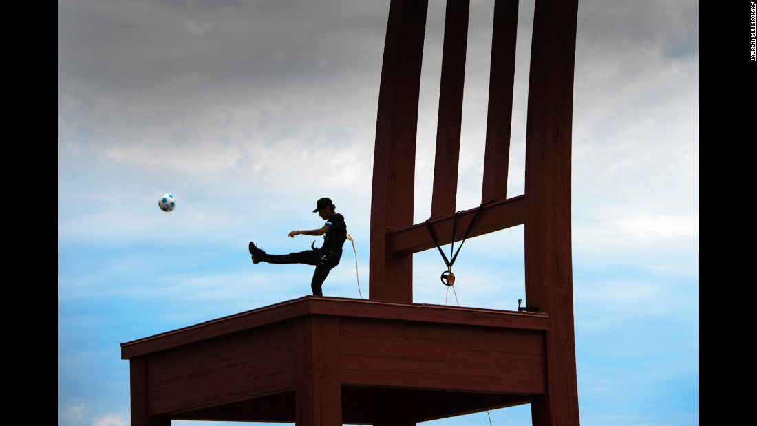 Brazilian soccer star Neymar kicks a ball off the Broken Chair sculpture in Geneva, Switzerland, on Tuesday, August 15. The sculpture is a symbol for landmine victims around the world.