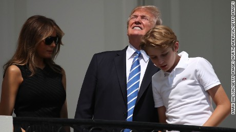 President Donald Trump looks up toward the Solar Eclipse while standing with his wife first lady Melania Trump and their son Barron, on the Truman Balcony at the White House on August 21, 2017 in Washington, DC.