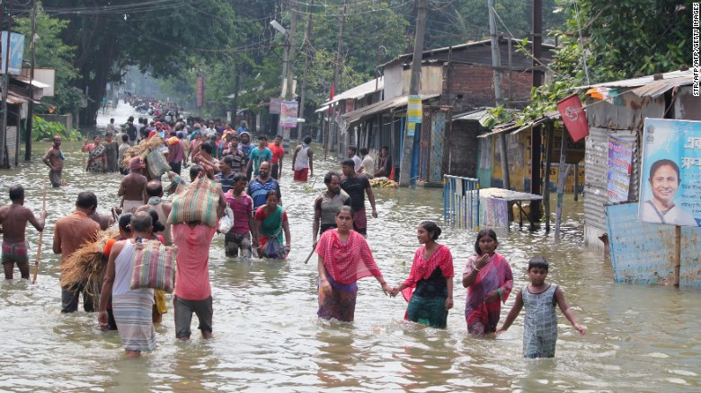 Residents wade through flood waters in the Indian state of West Bengal on August 17.