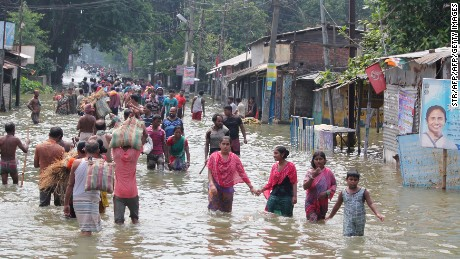 TOPSHOT - Indian residents wade through flood waters in Balurghat in West Bengal on August 17, 2017. At least 221 people have died and more than 1.5 million have been displaced by monsoon flooding across India, Nepal and Bangladesh, officials said August 15, as rescuers scoured submerged villages for the missing. / AFP PHOTO / STR        (Photo credit should read STR/AFP/Getty Images)