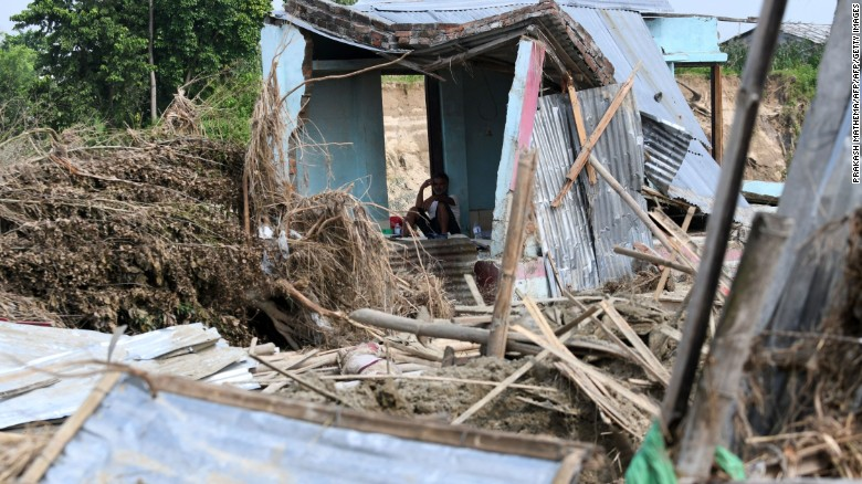 A man rests in his house damaged by flooding some 250 kilometers from Nepal's capital Kathmandu on August 16.