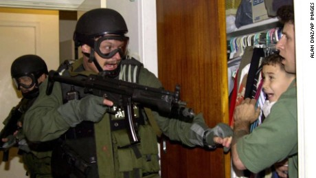 In this third of seven sequential photos, Elian Gonzalez is held in a closet by Donato Dalrymple, one of the two men who rescued the boy from the ocean, right, as government officials search the home of Lazaro Gonzalez for the young boy, early Saturday morning, April 22, 2000, in Miami. Armed federal agents seized Elian Gonzalez from the home of his Miami relatives before dawn Saturday, firing tear gas into an angry crowd as they left the scene with the weeping 6-year-old boy.