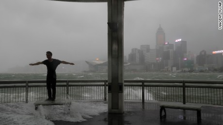 A man plays with strong wind caused by typhoon Hato on the waterfront of Victoria Habour in Hong Kong, Wednesday, Aug. 23, 2017. A powerful typhoon barreled into Hong Kong on Wednesday, forcing offices and schools to close and leaving flooded streets, shattered windows and hundreds of canceled flights in its wake.  (AP Photo/Vincent Yu)