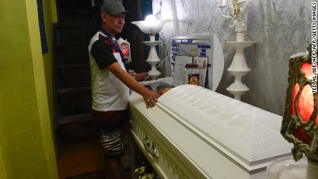 Saldy Delos Santos, father of the 17 year-old student Kian Loyd stands next to the coffin of his son, allegedly killed by a police anti-drug raid, during a wake at his home in Manila on August 18, 2017.