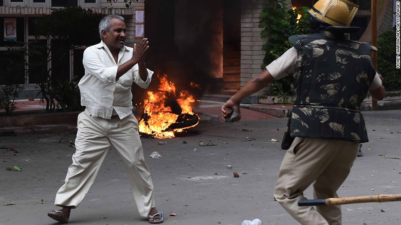 A follower of Indian religious leader Gurmeet Ram Rahim Singh pleads for his safety after being hit with a stick during clashes between the controversial guru's followers and security forces in Panchkula on August 25, 2017.