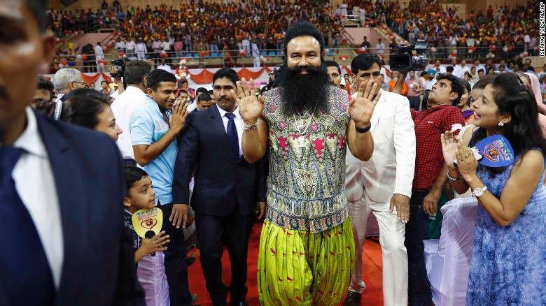 Gurmeet Ram Rahim Singh, center, greets followers as he arrives for a press conference in New Delhi, India, in October 2016.