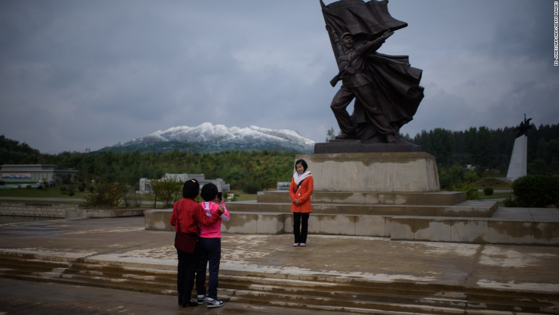 <strong>Moving mountains: </strong>Tourists pose with a miniature statue, in front of a model of Mount Paektu (an active volcano) at a folk park on the outskirts of Pyongyang.