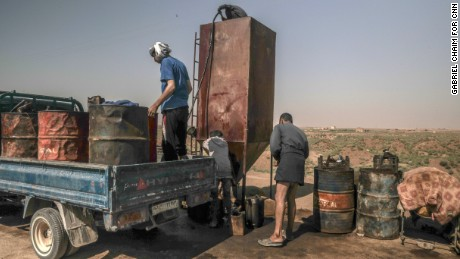 Local residents refuel at an improvised gas station in a liberated area in west Raqqa on Friday.
