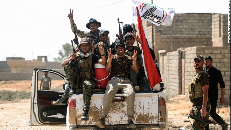 Fighters of the Popular Mobilisation Units flash the victory gesture as they sit in the back of a pickup truck during the advance in the eastern part of Tal Afar on Friday.