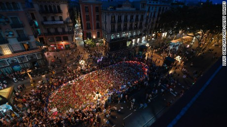 People gather around a flower tribute on Las Ramblas on Saturday to remember the victims of last week's deadly attacks.