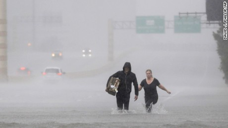 Two people walk down a flooded section of Interstate 610 in floodwaters from Tropical Storm Harvey on Sunday, Aug. 27, 2017, in Houston.