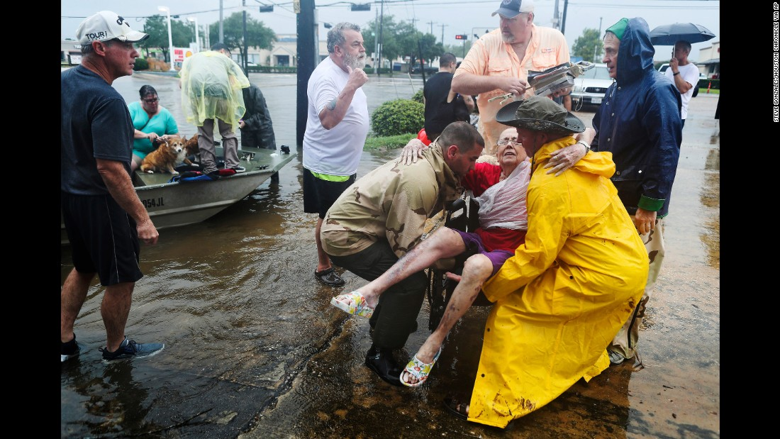 Jane Rhodes is rescued by neighbors in Friendswood, Texas, on August 27.