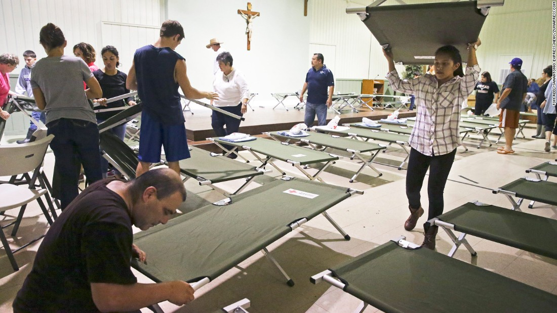 Volunteers at Sacred Heart Catholic Church prepare cots for evacuees in Elgin, Texas, on August 27.