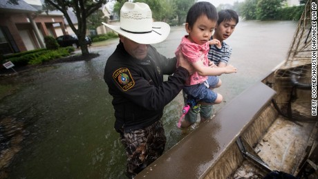 Fort Bend County Sheriff Troy Nehls and Lucas Wu lift Ethan Wu into an airboat as they are evacuated at the Orchard Lakes subdivision in Fort Bend County, Texas, on August 27.