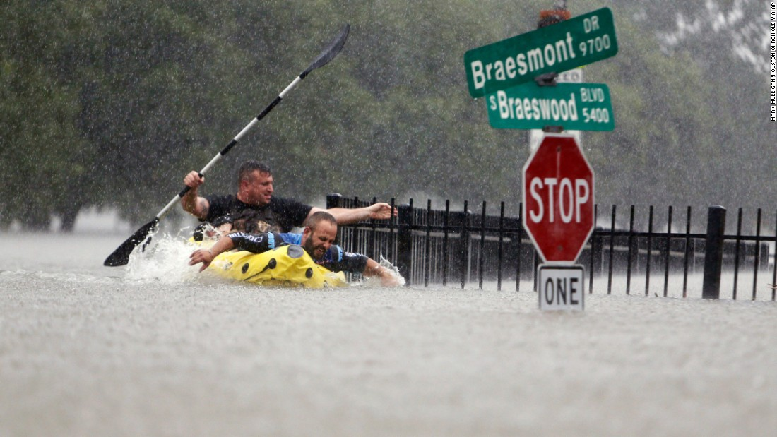 Two men try to beat the current that was pushing them down an overflowing Brays Bayou in Houston on August 27.