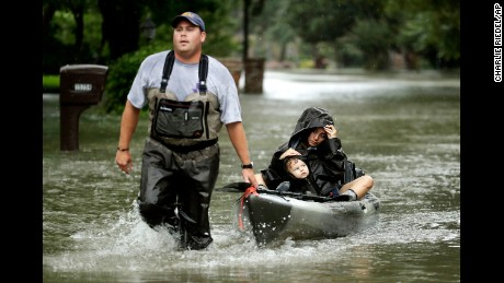 People evacuate a neighborhood in west Houston on Monday, August 28.