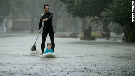 Alexendre Jorge evacuates Ethan Colman, 4, from a neighborhood in Houston on August 28.