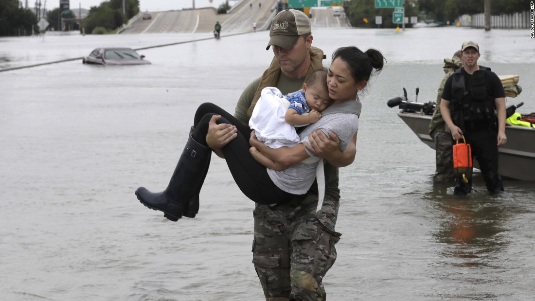 Houston police officer Daryl Hudeck carries Catherine Pham and her 13-month-old son, Aiden, after rescuing them from floodwaters on Sunday, August 27.