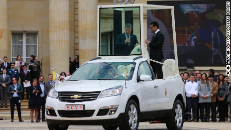 "Colombian President Juan Manuel Santos (L) stands inside one of three ""popemobiles"" to be used by Pope Francis during his upcoming visit to Colombia, as they are unveiled during the official launching of the pontiff's visit, at the Narino presidential palace in Bogota on August 28, 2017. Pope Francis will make a four-day visit to Colombia, from September 6-11, to add his weight to the process of reconciliation between the government and the Revolutionary Armed Forces of Colombia (FARC).  / AFP PHOTO / John Vizcaino        (Photo credit should read JOHN VIZCAINO/AFP/Getty Images)"