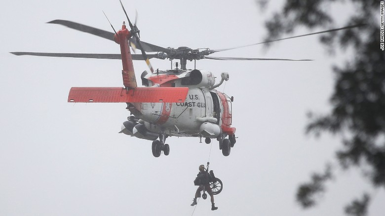 A Coast Guard helicopter hoists a wheel chair on board after lifting a person to safety from the flooded area in Houston on August 28.