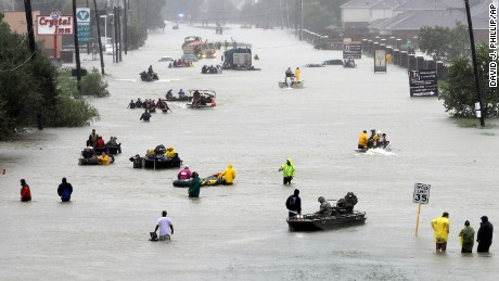 Rescue boats fill a flooded street as people are evacuated in Houston on August 28.