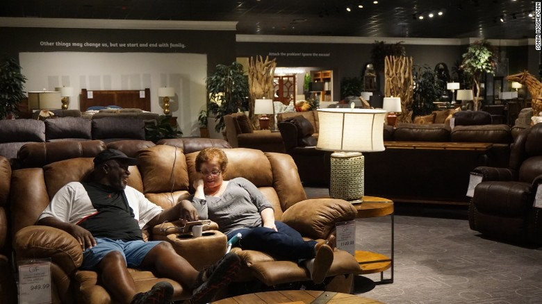 David And Maria Parks Sit On A Couch In The Gallery Furniture Showroom,  Watching Local