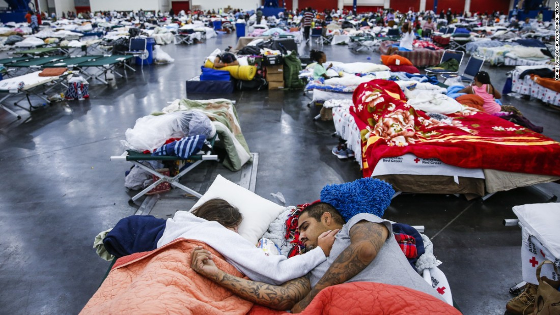 Tammy Dominguez, left, and her husband, Christopher Dominguez, sleep on cots at the George R. Brown Convention Center, where nearly 10,000 people are taking shelter in Houston, on August 30.