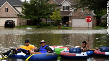 Rescue volunteers relax after clearing out all the evacuees from the Twin Oaks Estate in the Clodine district after Hurricane Harvey caused heavy flooding in Houston, Texas on August 29, 2017.   Harvey has set what forecasters believe is a new rainfall record for the continental US, officials said Tuesday. Harvey, swirling for the past few days off Texas and Louisiana has dumped more than 49 inches (124.5 centimeters) of rain on the region.  / AFP PHOTO / MARK RALSTON        (Photo credit should read MARK RALSTON/AFP/Getty Images)