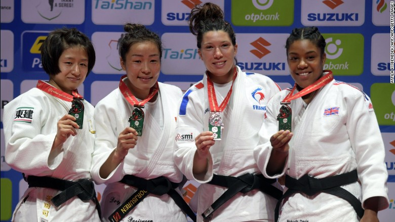 Japan's Tsukasa Yoshida, Mongolia's Sumiya Dorjsuren, France's Helene Receveaux and Great Britain's Nekoda Smythe-Davis show off their medals in the women's -57kg division.