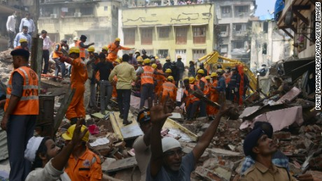 Rescue workers and residents look for survivors at the site of a building collapse in Mumbai on August 31, 2017. At least three people died and dozens were feared trapped when a building collapsed in India's financial capital of Mumbai on August 31, after days of heavy rain swamped the city. / AFP PHOTO / PUNIT PARANJPE        (Photo credit should read PUNIT PARANJPE/AFP/Getty Images)