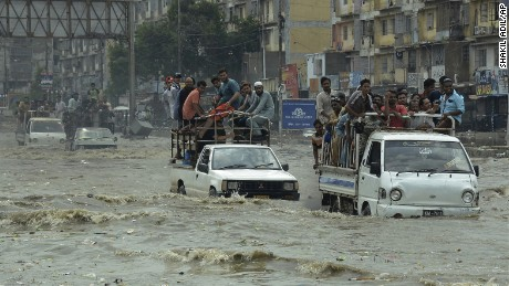 Pakistani commuters travel on a flooded street following a heavy rainfall in Karachi, Pakistan, Thursday, Aug. 31, 2017.