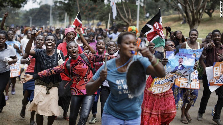 Supporters of opposition leader Raila Odinga celebrate in Uhuru Park, some carrying Kenyan flags and posters of Odinga.