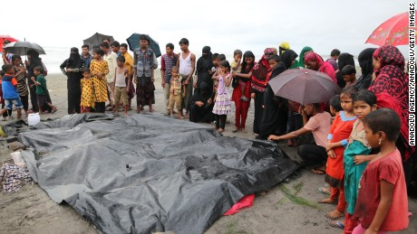 People gather around covered dead bodies of Rohingya children who died after a boat carrying Rohingya people capsized.