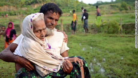 A Rohingya man carrying his mother after crossing the Bangladesh-Myanmar border.