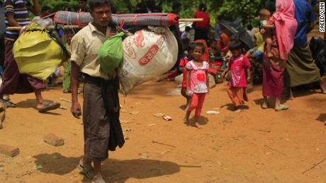 A Rohingya man, carrying what he could from his home in Rakine, walks towards the Kutupalang unregistered camp to look for shelter.