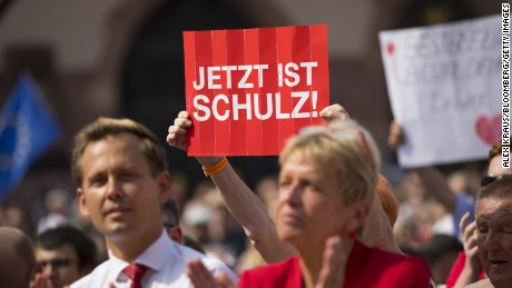 "An SPD supporter holds up a ""Now Is Schulz"" poster at a campaign rally."