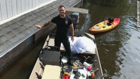 Kyle Parry outside his flooded home, with his fiancee's wedding dress safely aboard his boat.