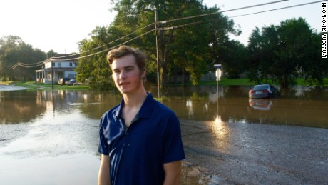 Shane Singleton waded through floodwaters pulling a boat to help neighbors.