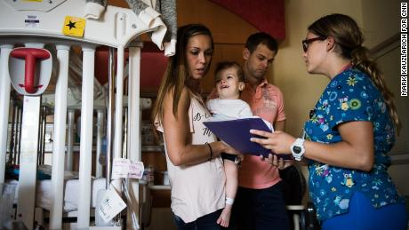 Nicole McDonald holds her son Jadon while looking over discharge information as they prepare to leave the rehab facility on September 1.