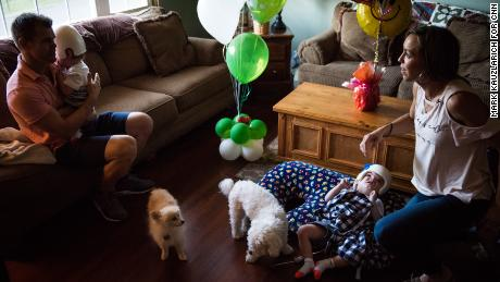 Christian McDonald holds his son Anias as Nicole McDonald checks on Jadon at home with the family dogs, Taz and Tyson.