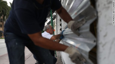 Winston Mora, left, and Gus Sousa put hurricane shutters on a business Wednesday in Miami.