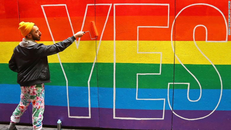 Artist David Lee Pereira paints a pro-gay marriage mural on a wall at Melbourne Central on August 27.