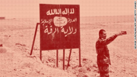 A picture taken on July 9, 2017 shows a Syrian regime forces member taking a selfie with an Islamic State (IS) group billboard at the Ithraya-Rasafa highway in the countryside of the city of Raqa. 