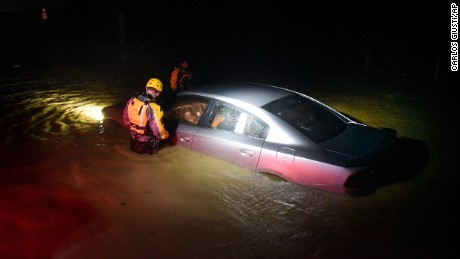 First responders check an empty car caught in floodwaters Wednesday in Fajardo, Puerto Rico.