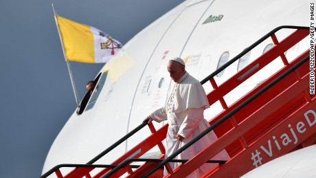 "Pope Francis descends from the plane upon touching down in Bogota on September 6, 2017.  Pope Francis arrived in Colombia for a five-day tour to plead for a ""stable and lasting"" peace in a divided country just emerging from a 50-year war that claimed hundreds of thousands of lives. / AFP PHOTO / Alberto PIZZOLI        (Photo credit should read ALBERTO PIZZOLI/AFP/Getty Images)"