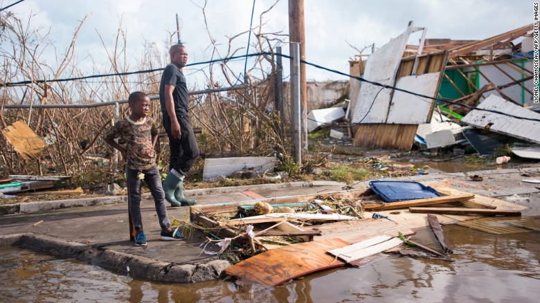 A man and a boy take a look at the damage Irma brought on September 7, in Marigot, near the Bay of Nettle, on the island of St. Martin.