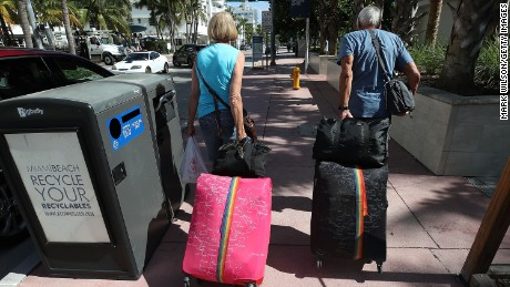 Tourist Bjorg Aasen and Arne Forsmo walk to catch a shuttle to a shelter on Friday in Miami Beach.