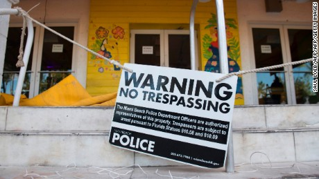 "A sign warns about trespassing as residents and tourists evacuate Miami Beach, Florida, September 7, 2017, ahead of Hurricane Irma. Hurricane Irma will have a ""truly devastating"" impact when it slams into southern coastal areas of the United States, the head of the US emergency agency said.  / AFP PHOTO / SAUL LOEB        (Photo credit should read SAUL LOEB/AFP/Getty Images)"