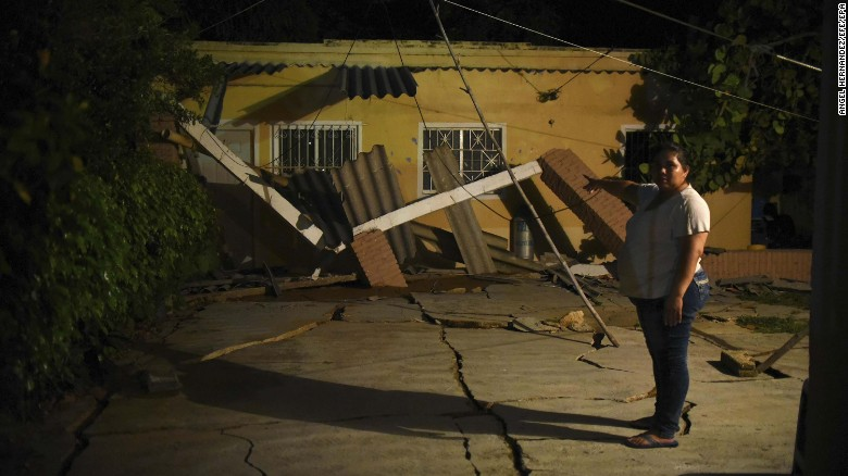 A woman gestures toward her earthquake-damaged home in Coatzacoalcos, in the state of Veracruz, Mexico.