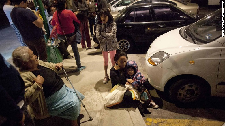 Residents sit on a sidewalk in Mexico City following the quake.